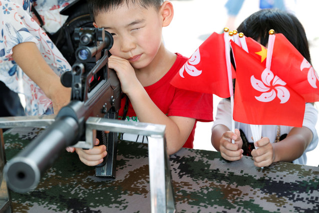 A child plays with a gun during an open day of Stonecutters Island naval base, in Hong Kong, China, June 30, 2019. (Photo by Tyrone Siu/Reuters)