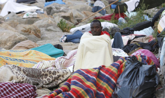A migrant is awake while others sleep on the rocky beach at the Franco-Italian border near Menton, southeastern France Wednesday, June 17, 2015. European Union nations failed to bridge differences Tuesday over an emergency plan to share the burden of the thousands of refugees crossing the Mediterranean Sea, while on the French-Italian border, police in riot gear forcibly removed dozens of migrants. (AP Photo/Lionel Cironneau)