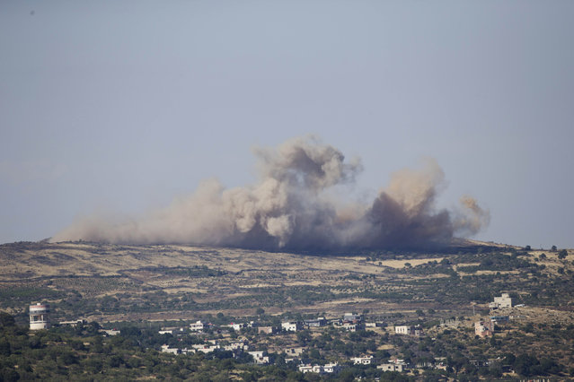 Smoke and explosions from the fighting between forces loyal to Syrian President Bashar Assad and rebels in the Druze village of Khader in Syria, as seen from the Israeli controlled Golan Heights, Tuesday, June 16, 2015. As many as 20 members of the Druze minority sect were killed last week, the deadliest violence against the Druze since Syria's conflict started in March 2011, sparking fears of a massacre against the sect. (AP Photo/Ariel Schalit)