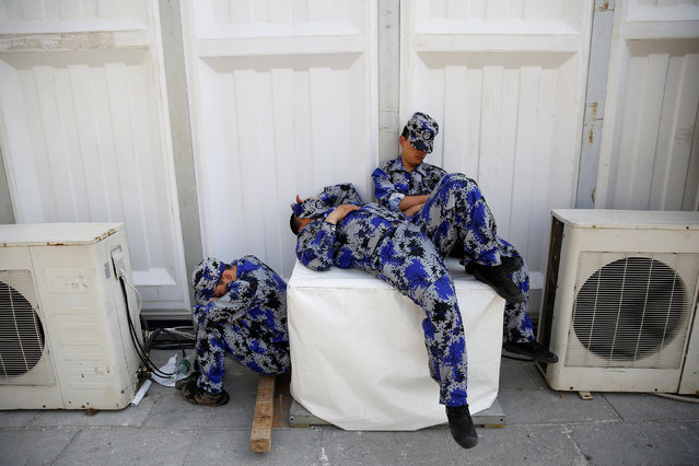 Security personnel take a nap behind one of the halls of Auto China 2016 auto show in Beijing April 25, 2016. (Photo by Damir Sagolj/Reuters)
