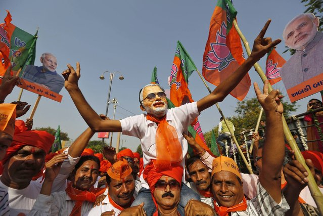 A supporter wearing a mask of Hindu nationalist Narendra Modi, prime ministerial candidate for India's main opposition Bharatiya Janata Party (BJP), cheers as Modi arrives to file nomination papers for the general elections in Vadodara in the western Indian state of Gujarat April 9, 2014. (Photo by Amit Dave/Reuters)