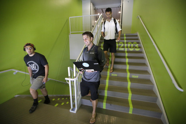 Utah Valley University students walks along the bright green lanes painted on the stairs to the gym Thursday, June 18, 2015, at Utah Valley University, in Orem, Utah. Utah Valley University spokeswoman Melinda Colton said  the green lanes were intended as a lighthearted way to brighten up the space and get students attention. (AP Photo/Rick Bowmer)