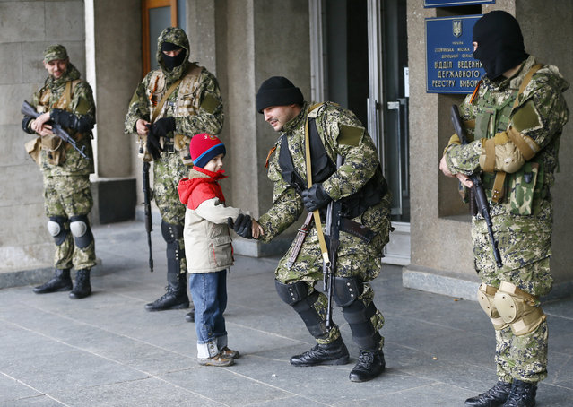 """A boy shakes hands with a pro-Russian armed man outside the mayor's office in Slaviansk April 14, 2014. Pro-Russian separatists who said they were part of a new """"Donetsk People's Republic"""" in eastern Ukraine appealed on Monday for Russian President Vladimir Putin to help defend them against Ukrainian government forces. (Photo by Gleb Garanich/Reuters)"""