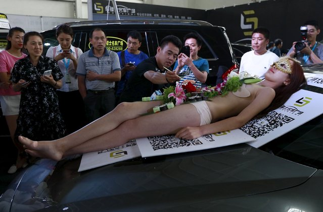 A man uses chopsticks to pick up sushi which was placed on the body of a model, during a promotional event at an automobile exhibition in Shenyang, Liaoning province, China, June 27, 2015. (Photo by Reuters/Stringer)
