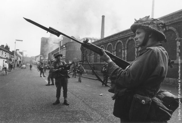 British soldiers on guard duty in the Falls area of Belfast, 1st October 1969. A mill is blazing in the background