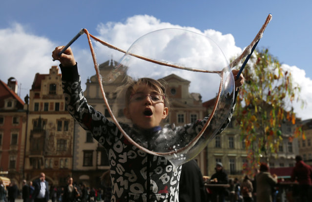 A young girl blows a bubble at the Old Town Square in Prague, Czech Republic, Monday, April 14, 2014. (Photo by Petr David Josek/AP Photo)
