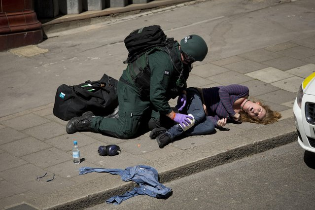 During a training exercise for London's emergency services, a medic treats a casualty, outside the disused Aldwych underground train station in London, Tuesday, June 30, 2015. (Photo by Matt Dunham/AP Photo)