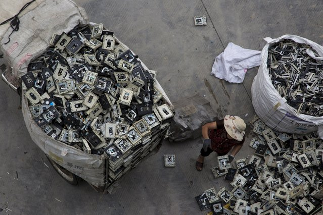 A worker distributes electronic waste at a government managed recycling centre at the township of Guiyu in China's southern Guangdong province June 10, 2015. (Photo by Tyrone Siu/Reuters)