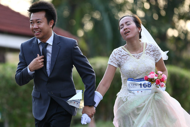 "A couple participates in the ""Running of the Brides"" race in a park in Bangkok, Thailand March 25, 2017. (Photo by Athit Perawongmetha/Reuters)"