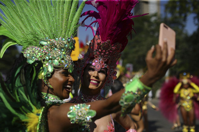 Dancers take a selfie as they wait to perform during the the Notting Hill Carnival in west London, Monday August 26, 2019. The annual carnival event parades through the streets surrounding the Notting Hill area of London. (Photo by Aaron Chown/PA Wire via AP Photo)
