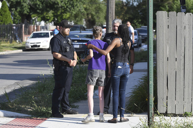 Deborah Golden, center, talks with Detroit police after she tried to render aid to a young girl who later died of her injuries in Detroit on Monday, August 19, 2019. Police say the owner of three dogs is in custody after the animals killed Emma Hernandez, 9, as she rode a bike. The girl's father, Armando Hernandez, says the man was warned that a fence was too flimsy to hold the dogs.  (Photo by Max Ortiz/Detroit News via AP Photo)