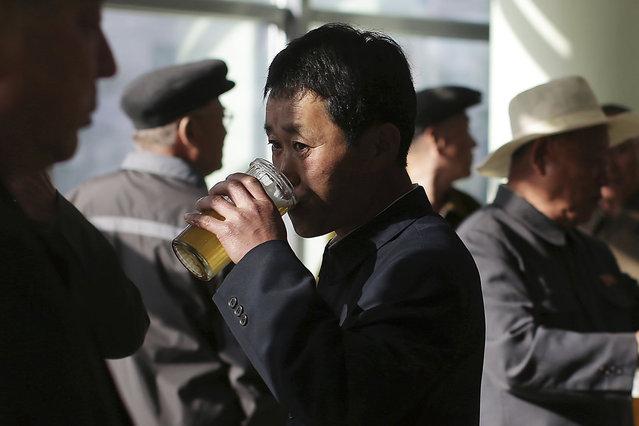 In this Saturday, May 7, 2016, photo, North Korean men drink beer at the Taedonggang Beer shop in Pyongyang, North Korea. (Photo by Wong Maye-E/AP Photo)