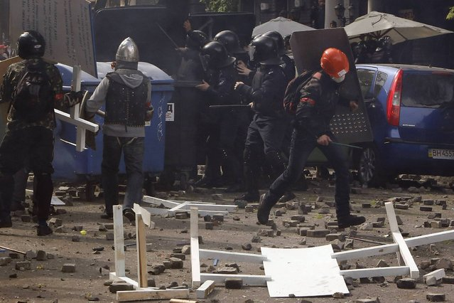 Police take cover as pro-Russian activists and supporters of the Kiev government clash in the streets of Odessa May 2, 2014. (Photo by Yevgeny Volokin/Reuters)