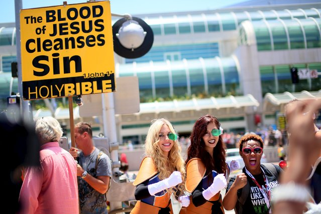Cosplayers pose for pictures while a picketer holds a pro-religion sign outside of the Convention Center at the 2015 Comic-Con International in San Diego, California July 9, 2015. (Photo by Sandy Huffaker/Reuters)
