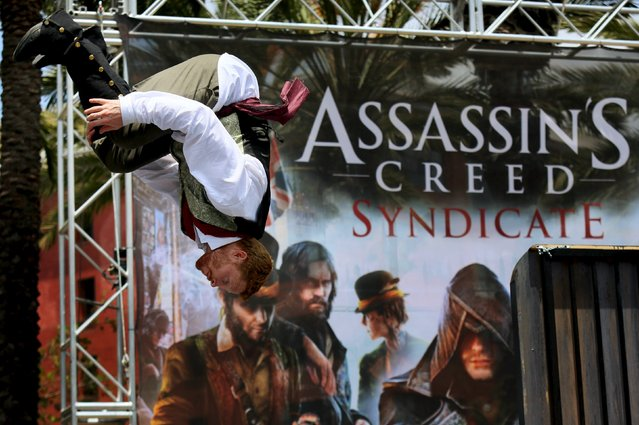"""A performer does a flip during an obstacle course at the """"Assassin's Creed Syndicate"""" booth outside of the 2015 Comic-Con International in San Diego, California July 10, 2015. (Photo by Sandy Huffaker/Reuters)"""