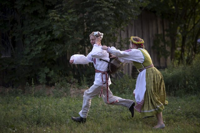 """People run as they take part in the festival of national traditions """"Piatrovski"""" in the village of Shipilovichi, south of Minsk, July 12, 2015. (Photo by Vasily Fedosenko/Reuters)"""