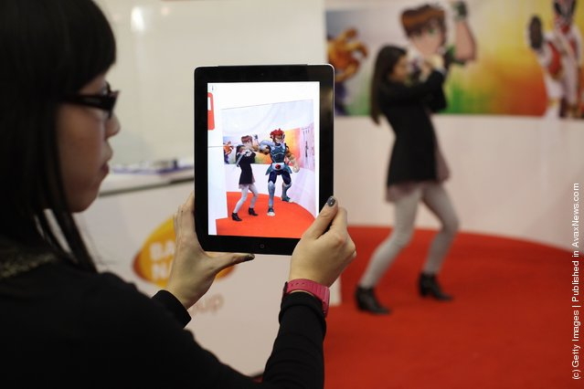 A woman uses the Aurasma app on an iPad which displays a virtual 3D animation of a Thundercat character which her colleague pretends to fight at the 2012 London Toy Fair
