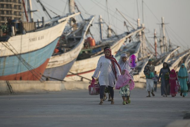 Muslims walk near traditional Indonesian Phinisi ships on their way to Eid al-Fitr prayers at Sunda Kelapa port in Jakarta, Indonesia July 17, 2015. (Photo by Darren Whiteside/Reuters)