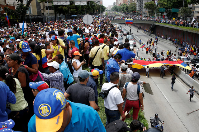 Opposition supporters carrying Venezuelan flags take part in a rally to demand a referendum to remove President Nicolas Maduro in Caracas, Venezuela, May 18, 2016. (Photo by Carlos Garcia Rawlins/Reuters)