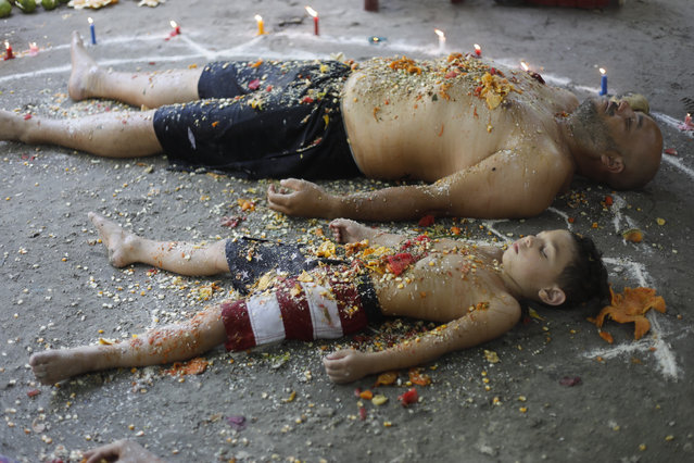 In this photo taken October 13, 2019, a man and boy lie with their eyes closed amid candles inside a circle, called an oracle, made of white powder during a ritual for prosperity on Sorte Mountain where followers of indigenous goddess Maria Lionza gather annually in Venezuela's Yaracuy state. Venezuela is predominantly Roman Catholic, whose church disapproves of the folk religion but has long since abandoned its attempts to suppress it. (Photo by Ariana Cubillos/AP Photo)