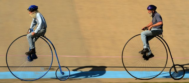Men ride penny farthing bicycles during the 2017 Sydney Classic Bicycle Show at Canterbury Velodrome in Sydney on May 6, 2017. The Sydney Classic Bicycle Show is in its fifth year and is run by the Dulwich Hill Bicycle Club, which was started in 1908 and showcases bicycles from the 1800s to the present day. (Photo by Peter Parks/AFP Photo)