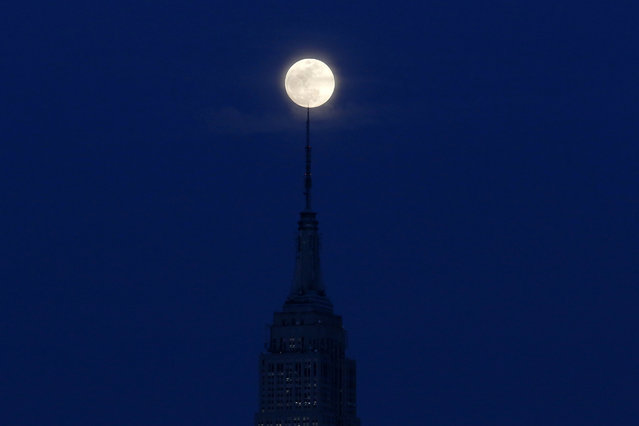 The moon is seen in its waxing stage as it rises over the Empire State Building, seen from the Hudson River waterfront in Hoboken, N.J., Tuesday, March 22, 2016. (Photo by Julio Cortez/AP Photo)