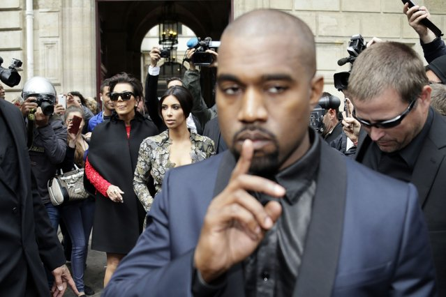 Kanye West walks in front of his fiancee, Kim Kardashian, and her mother, Kris Jenner, as they leave their hotel in Paris, on May 23, 2014. (Photo by Kenzo Tribouillard/AFP Photo)