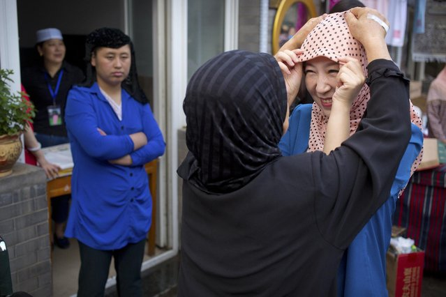 A woman helps a Chinese Muslim woman adjust her headscarf before Eid al-Fitr prayers at the Niujie mosque, the oldest and largest mosque in Beijing, Saturday, July 18, 2015. The Eid al-Fitr celebrations mark the end of the Muslim holy fasting month of Ramadan. (Photo by Mark Schiefelbein/AP Photo)