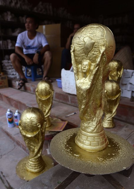 A customer waits for replicas of the football World Cup trophy at a shop in Bat Trang pottery village on the outskirts of Hanoi on June 12, 2014. The trophies are sold for about 3.5 US dollars to local football fans. (Photo by Hoang Dinh Nam/AFP Photo)