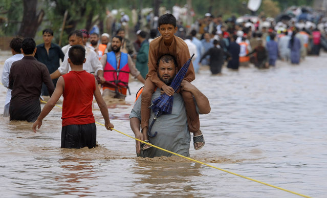 A Pakistani carries his son on his shoulder while he and others cross a flooded road caused by heavy rains in Peshawar, Pakistan, Sunday, July 26, 2015. Heavy monsoon rains lashed an already-deluged northern Pakistan before dawn Saturday, so far killing tens of people in different parts of the country. (Photo by Muhammad Sajjad/AP Photo)