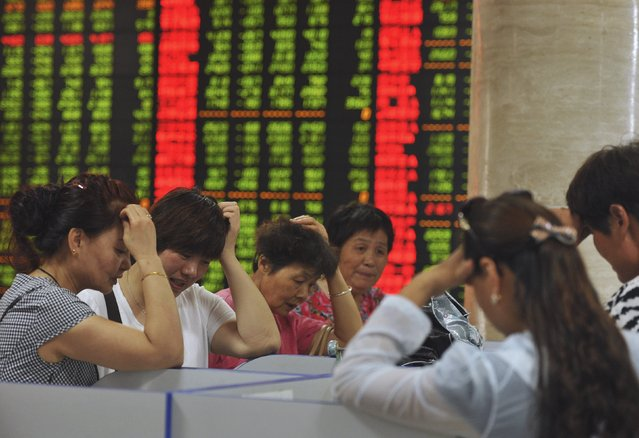 Investors react as they look at computer screens showing stock information at a brokerage house in Fuyang, Anhui province, China, July 28, 2015. Chinese shares fell on Tuesday, as Beijing scrambled once again to prop up a stock market whose wild gyrations have heightened fears about the financial stability of the world's second biggest economy. (Photo by Reuters/Stringer)