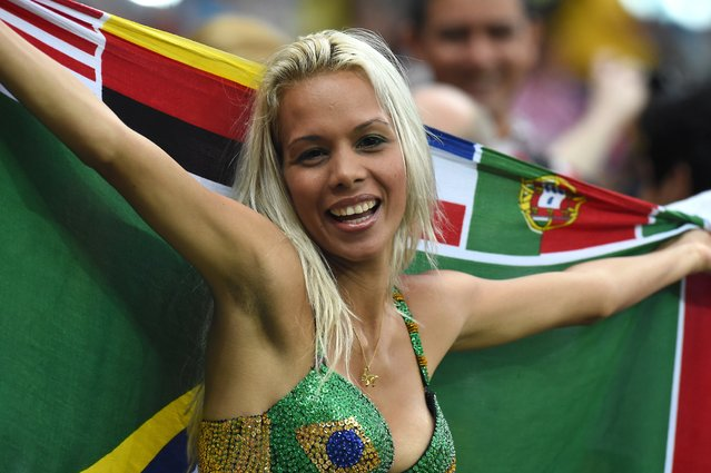 A supporter poses with the Brazilian flag ahead of the Group A football match between Cameroon and Croatia at The Amazonia Arena in Manaus on June 18, 2014, during the 2014 FIFA World Cup. (Photo by Javier Soriano/AFP Photo)