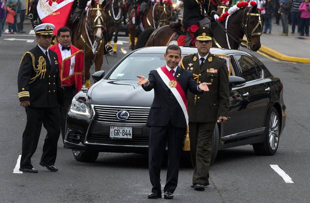 Peru's President Ollanta Humala, gestures to the press to move back and give him space to walk to deliver his last State of the Nation address to congress during Independence Day in Lima, Peru, Tuesday, July 28, 2015. President Humala walked the distance from the national palace to congress. (Photo by Martin Mejia/AP Photo)