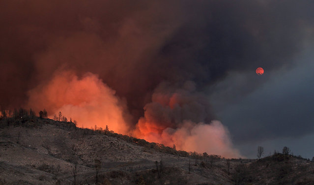 In this Thursday, July 30, 2015, photo, fire blazes as smoke tints the view of the moon rising over the Rocky Fire near Lower Lake, Calif. Several new blazes flared up Thursday, forcing hundreds of people from their homes. (Photo by Kent Porter/The Press Democrat via AP Photo)
