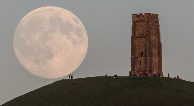 The moon rises over people gathered on Glastonbury Tor ahead of tomorrow's Blue Moon on July 30, 2015 in Somerset, England. The full moon appearing on July 31 will be what's called a Blue Moon, which refers to the second of two full moons appearing in the same calendar month. The last time this happened was in 2012 and there isn't due another until 2018. (Photo by Matt Cardy/Getty Images)