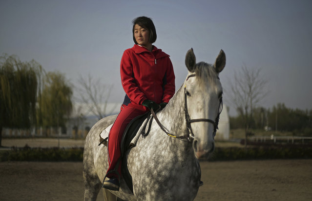 In this April 20, 2017, photo, Pak Hyon Sun, 18, poses on a horse at the Mirim Riding Club, in Pyongyang, North Korea. Pak has been a riding instructor for one year and she hopes to become an expert one day at horse riding. (Photo by Wong Maye-E/AP Photo)