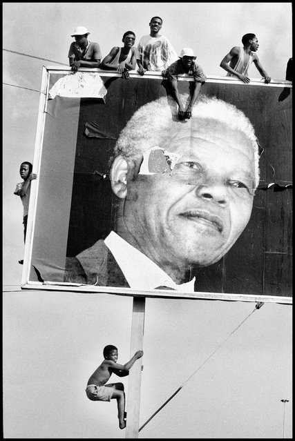 "Lamontville, Natal, South Africa, 1994. Supporters climb to every vantage point whilst awaiting the arrival of Nelson Mandela. Ian Berry writes: ""I went to South Africa three weeks before the election that everybody anticipated would bring the ANC and Mandela to power. Even this long before, my press accreditation was numbered over 300 ... Although, thousands of images later, I managed to get to him exclusively, this picture, perhaps not for me an HCB moment, best summed up the enthusiasm and support that Mandela invoked"". (Photo by Ian Berry/Magnum Photos)"