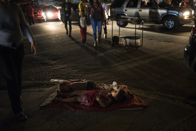 "Children sleep in the street near their mother's food stand where she sells food to people attending an event marking the feast day of Our Lady of Chiquinquirá, better know as ""Chinita"", in downtown Maracaibo, Venezuela, November 17, 2019. For many in Maracaibo, Venezuela's economic crash in the last five years hit especially hard. Once a center of the nation's vast oil wealth, production under two decades of socialist rule has plummeted to a fraction of its high, taking down residents' standard of living. (Photo by Rodrigo Abd/AP Photo)"