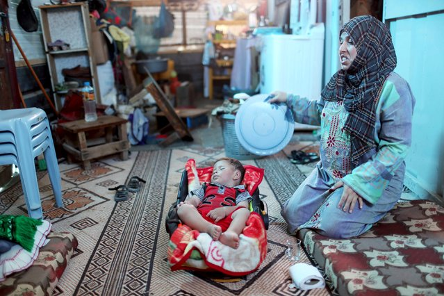 A Palestinian woman, whose house was destroyed by what witnesses said was Israeli shelling during a 50-day war last summer, uses a tray to fan her son during a wave of heat at her makeshift shelter in Khan Younis in the southern Gaza Strip August 3, 2015. (Photo by Ibraheem Abu Mustafa/Reuters)