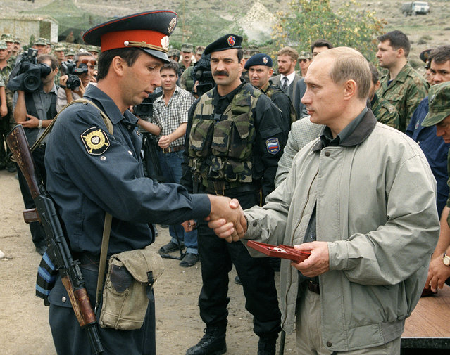 In this August 27, 1999 file photo, Russian Prime Minister Vladimir Putin, right, presents an award to a local police officer at a Russian military base in the mountains of the Botlikh region, Dagestan. Former Russian President Boris Yeltsin named the relatively little-known Vladimir Putin as his prime minister, on Aug. 9, 1999 days after Islamic militants based in Chechnya staged armed incursions into Dagestan. Russian forces entered Chechnya weeks after the attacks, starting the second of two post-Soviet wars in the mostly Muslim region and driving its separatist leadership from power. (Photo by AP Photo)