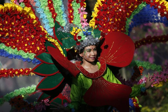 A Balinese dancer performs as she take part in a parade to mark the opening of an annual Bali Art Festival at a main road in Denpasar, Bali, Indonesia, 11 June 2016. Bali Art Festival runs from 11 June until 09 July 2016, and features hundreds of local and international performers. (Photo by Made Nagi/EPA)