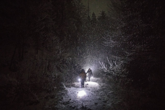 In this picture taken Thursday December 12, 2019, a group of Syrian refugees walk their way under a blizzard as they attempt to enter the EU through Croatia in the mountains surrounding the town of Bihac, northwestern Bosnia. (Photo by Manu Brabo/AP Photo)