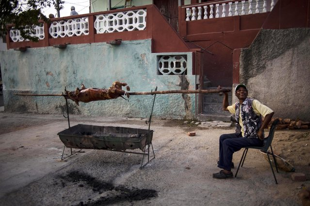 In this March 21, 2015 photo, a cook roasts a pig over a charcoal fire before the start of a neighborhood street party in Santiago, Cuba. He roasted it for about five hours to sell and serve to residents at the party. (Photo by Ramon Espinosa/AP Photo)