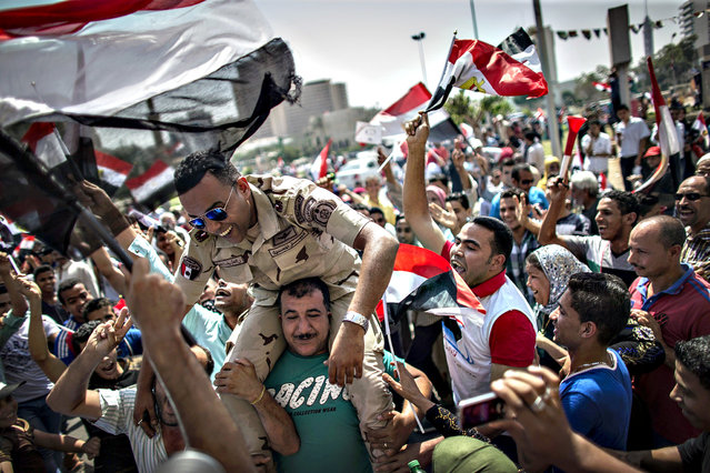 An Egyptian carries a member of the armed forces on his shoulders during celebrations of the opening of the new addition to the Suez Canal, in Tahrir Square, downtown Cairo, Egypt, 06 August 2015. The latest addition to the canal comes in at 72 kilometers (44 miles), was completed in under a year at an estimated cost of 8.5 billion US dollars, and was opened to shipping 06 August. (Photo by Oliver Weiken/EPA)