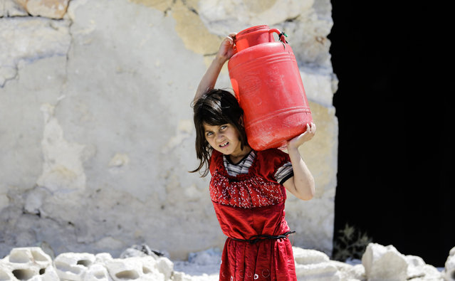 A Syrian girl carries a large jug of water on her back while on her way home, in the Kallaseh district of the northern city of Aleppo, on July 5, 2017. (Photo by Joseph Eid/AFP Photo)