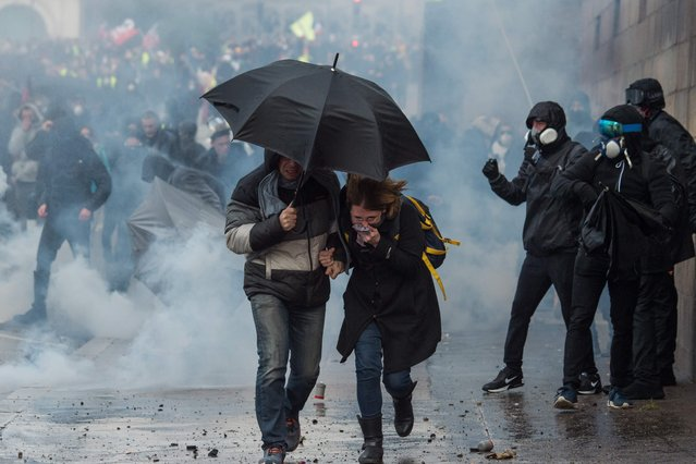 "People run for cover during a protest called by the ""Yellow Vest"" (gilets jaunes) anti-government movement as part of a nationwide multi-sector strike against the French government's pensions overhaul, on January 11, 2020 in Nantes, western France. France's government on January 11, 2020, offered a possible compromise to unions waging a crippling, weeks-long transport strike against pension reform, offering to withdraw the most contested proposal that would in effect have raised the retirement age by two years. ""To demonstrate my confidence in the social partners . I am willing to withdraw from the bill the short-term measure I had proposed"" to set a so-called ""pivot age"" of 64 with effect from 2027, Prime Minister Edouard Philippe wrote in a letter to union leaders a day after they met seeking to end the labour action, now in its 38th day. (Photo by Loic Venance/AFP Photo)"