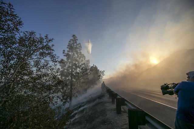 A Los Angeles County Fire Department helicopter drops water on a brush fire burning on the eastbound Ventura (134) Freeway in Los Angeles, California August 7, 2015. (Photo by Mario Anzuoni/Reuters)
