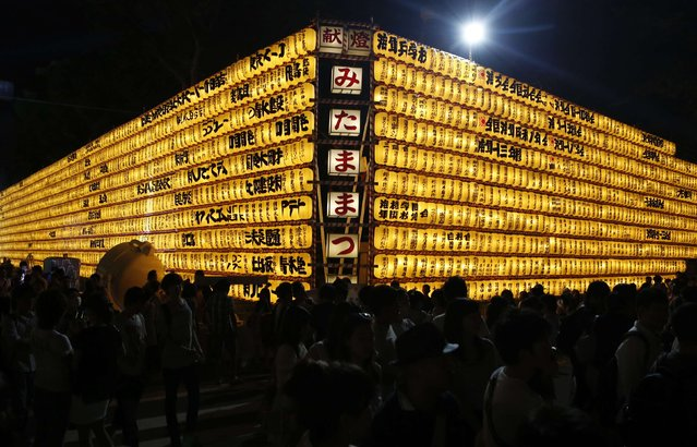 People walk in front of paper lanterns during the annual Mitama Festival at the Yasukuni Shrine in Tokyo July 13, 2014. Over 30,000 lanterns light up the precincts of the shrine, where more than 2.4 million war dead are enshrined, during the four-day festival. The festival goes on till July 16. (Photo by Yuya Shino/Reuters)