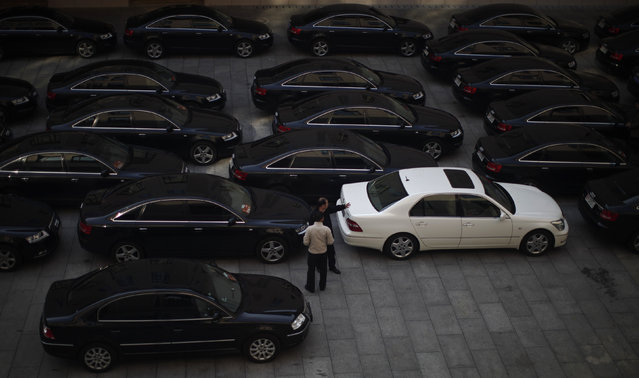 Drivers of government cars chat at a parking lot inside the Great Hall of the People, the venue of the 18th National Congress of the Communist Party of China, during the opening ceremony, in Beijing, China November 8, 2012. (Photo by Carlos Barria/Reuters)