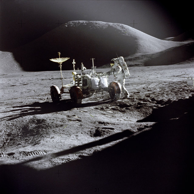 "Astronaut James B. Irwin, Lunar Module pilot, works at the Lunar Roving Vehicle during the first Apollo 15 lunar surface extravehicular activity (EVA-1) at the Hadley-Apennine landing site. The shadow of the Lunar Module ""Falcon"" is in the foreground. This view is looking northeast, with Mount Hadley in the background. This photograph was taken by Astronaut David R. Scott, Commander. (Photo by NASA)"